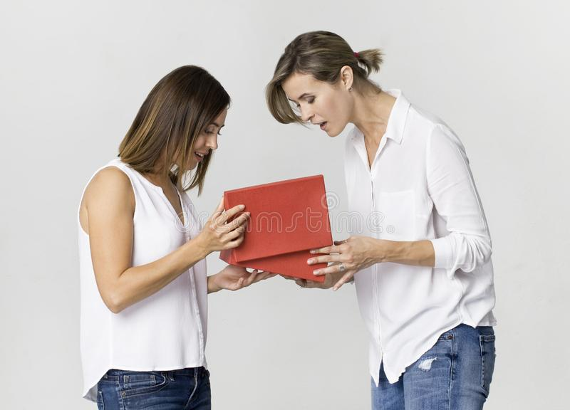 Young woman gives a gift to her friend. Smiling two women scene royalty free stock images
