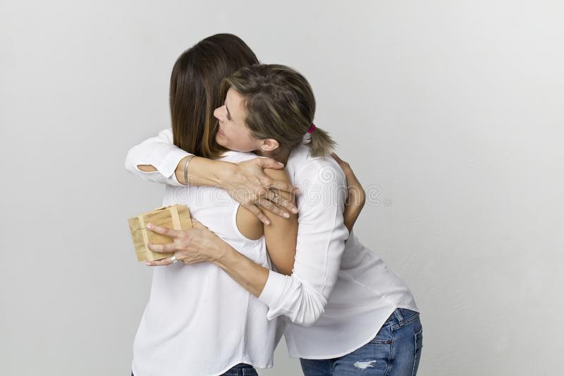 Young woman gives a gift to her friend. Smiling two women scene stock photography