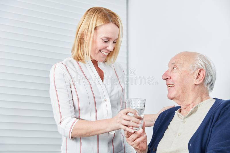 Young woman gives senior a glass of water stock images
