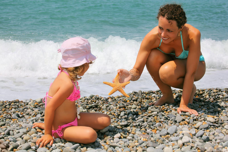 Young woman gives starfish to girl on beach royalty free stock photo