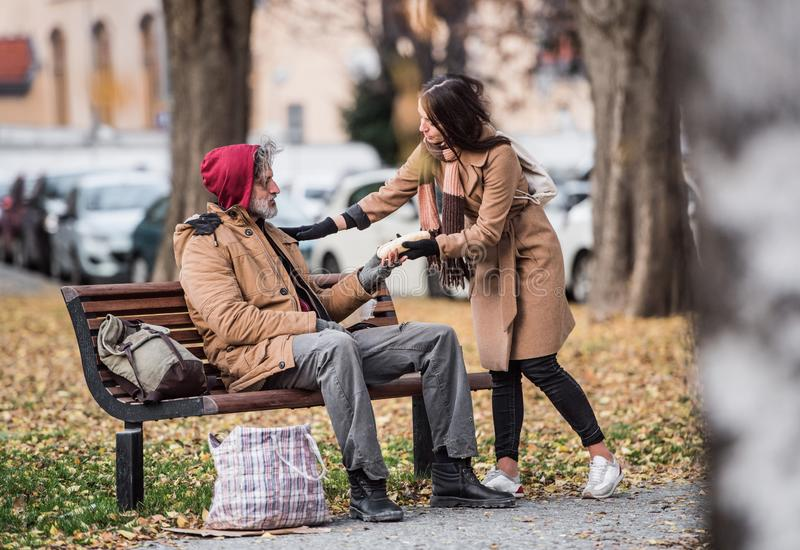Young woman giving food to homeless beggar man sitting on a bench in city. A young women giving food to homeless beggar men sitting on a bench outdoors in city stock image