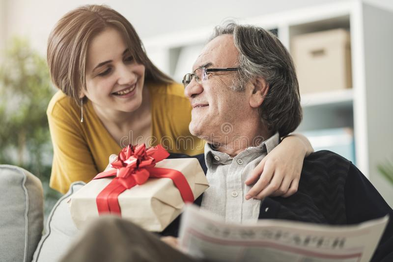 Young woman giving gift her father royalty free stock photos