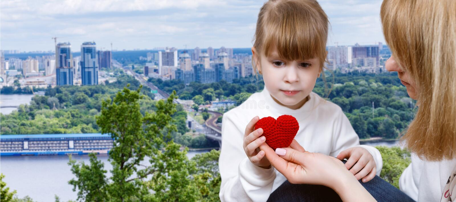 Young woman is giving a knitted heart to a small child royalty free stock images