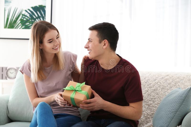 Young woman giving present to her beloved boyfriend at home stock images
