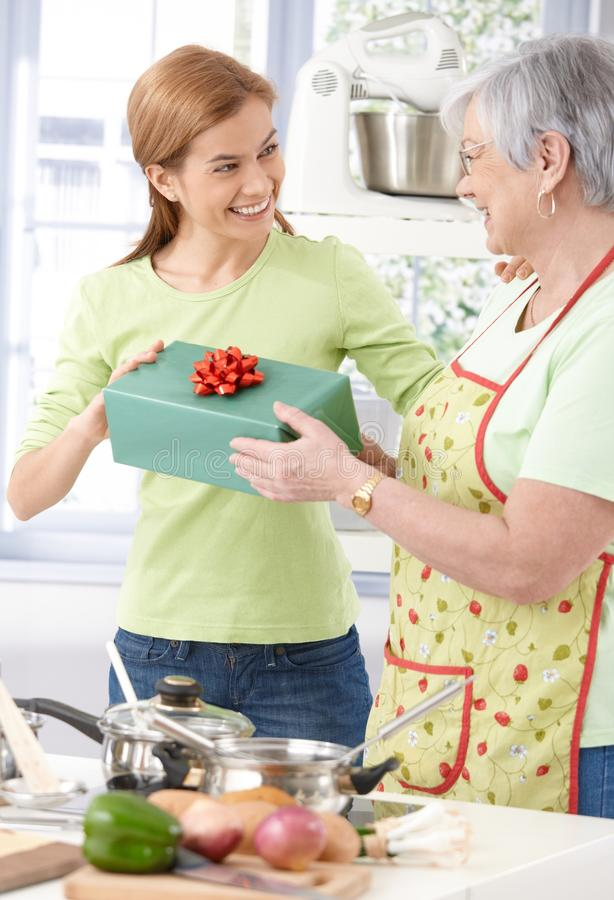 Young woman giving present to mother smiling stock images