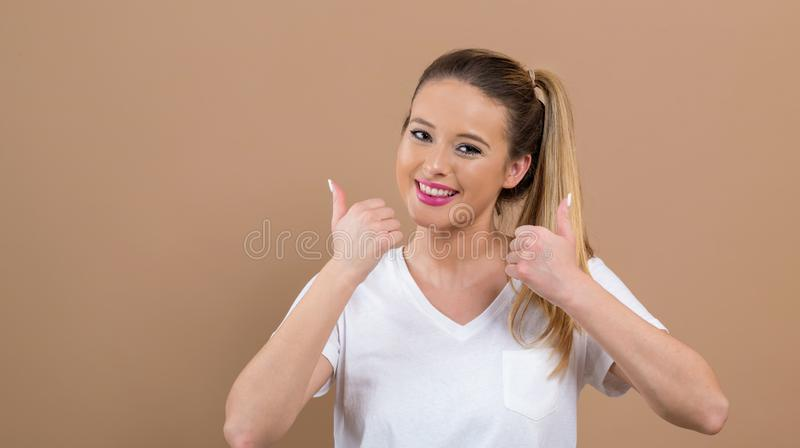 Young woman giving thumbs up stock photo