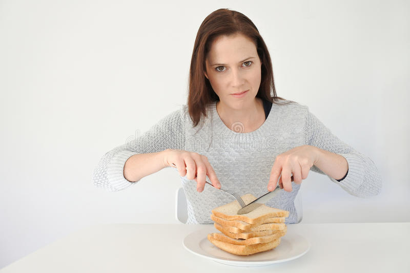 Young woman giving in to her urge and craving to Carbohydrates stock photography