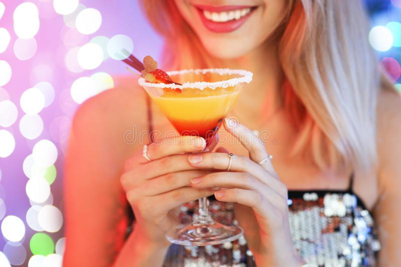 Young woman with glass of martini cocktail against festive lights. Closeup royalty free stock photography