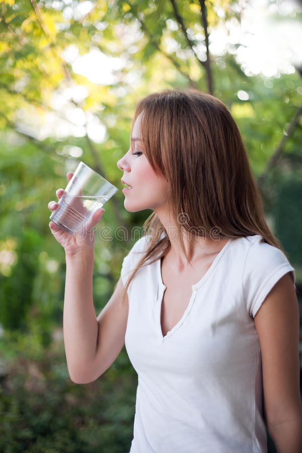 Beautiful young woman drinking water stock photos