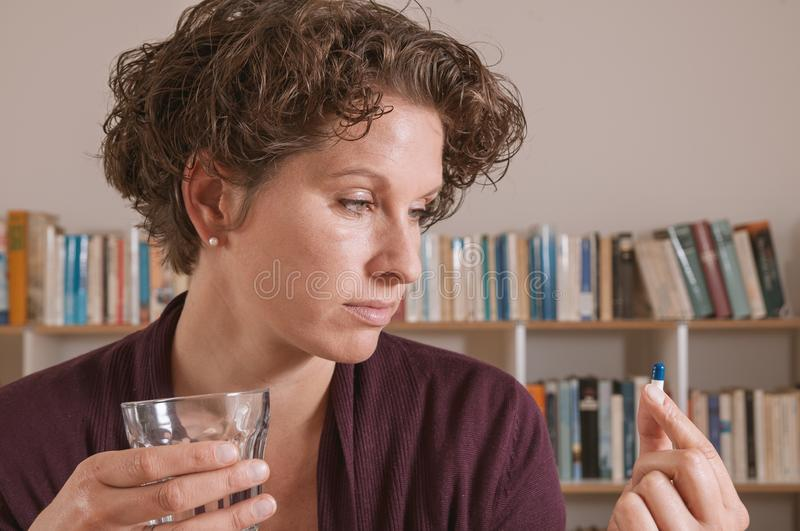Young woman worried about taking pill stock photo
