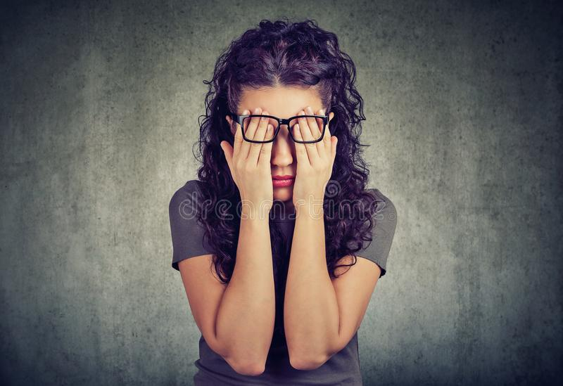 Young woman in glasses covering face eyes with both hands. Closeup portrait young woman in glasses covering face eyes with both hands isolated on gray wall stock image