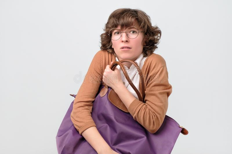 Young woman in glasses holding big bag. She is afraid to lose her shopping. Shopaholic concept royalty free stock images