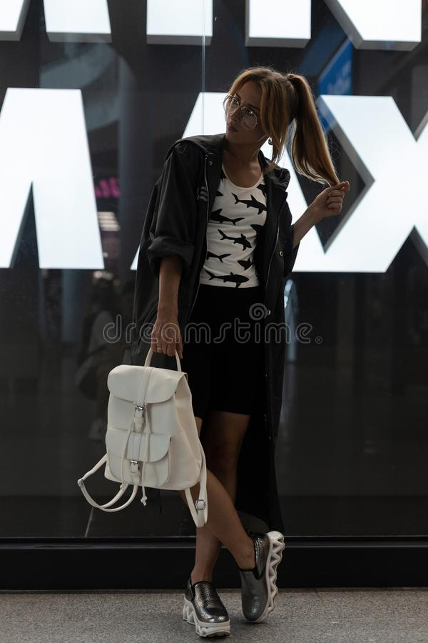 Young woman in a glasses in a raincoat in a trendy T-shirt with a pattern in vintage shiny shoes. With a stylish white leather backpack posing in a shopping royalty free stock photos