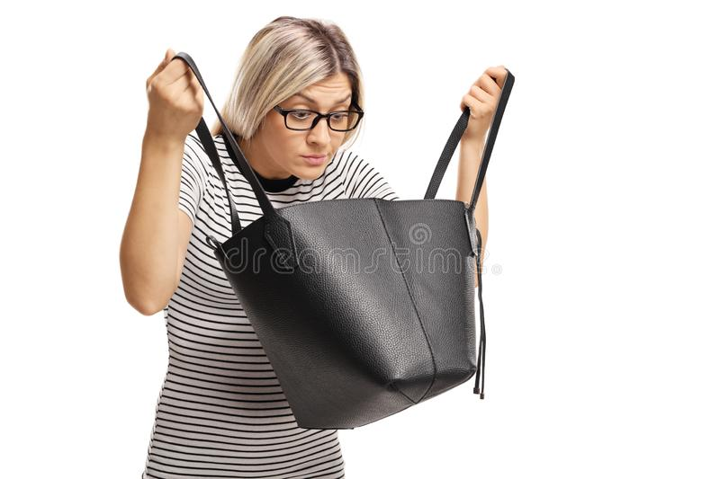 Young woman with glasses searching for something in her handbag royalty free stock photography