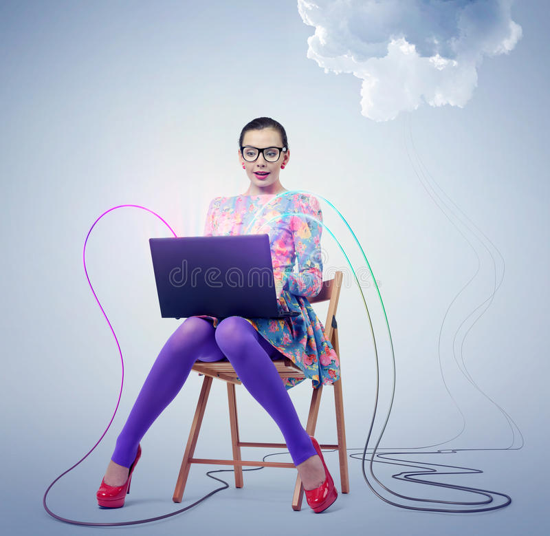 Young woman in glasses sitting on a chair with a laptop. Concept cloud computing. royalty free stock photos