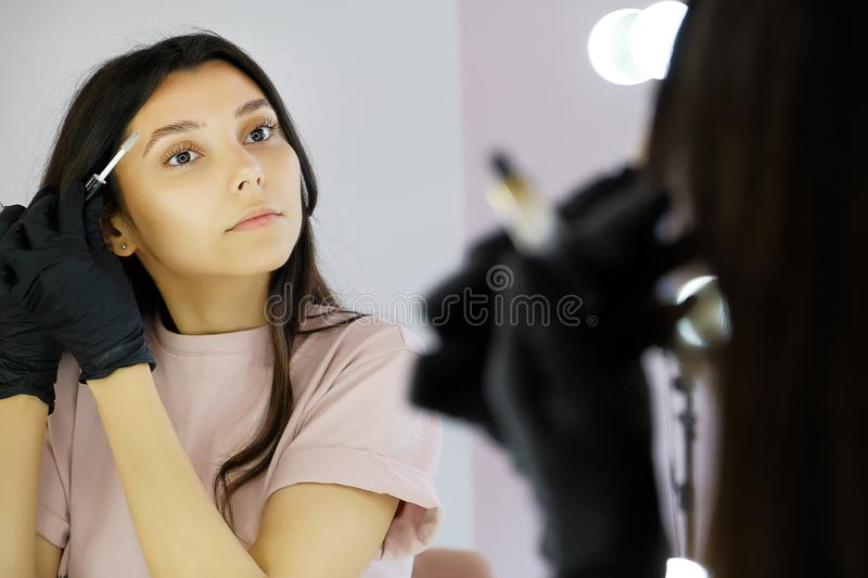 A young woman in gloves combs her eyebrows in a beauty salon, paints them with a brush before makeup. The concept of professional. Cosmetology, modeling and stock photo