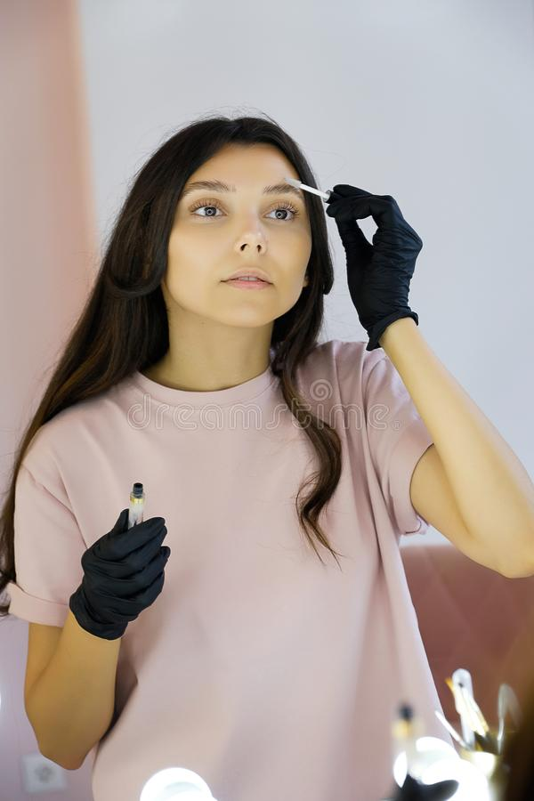 A young woman in gloves combs her eyebrows in a beauty salon, paints them with a brush before makeup. The concept of professional. Cosmetology, modeling and royalty free stock photography