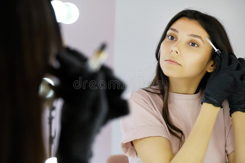 A young woman in gloves combs her eyebrows in a beauty salon, paints them with a brush before makeup. The concept of professional. Cosmetology, modeling and royalty free stock image