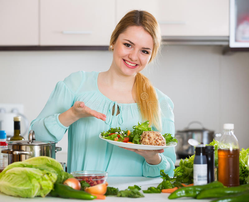 Young woman with goat cheese and vegetable mix. Positive woman with vegetable salad and cheese smiling at home royalty free stock images