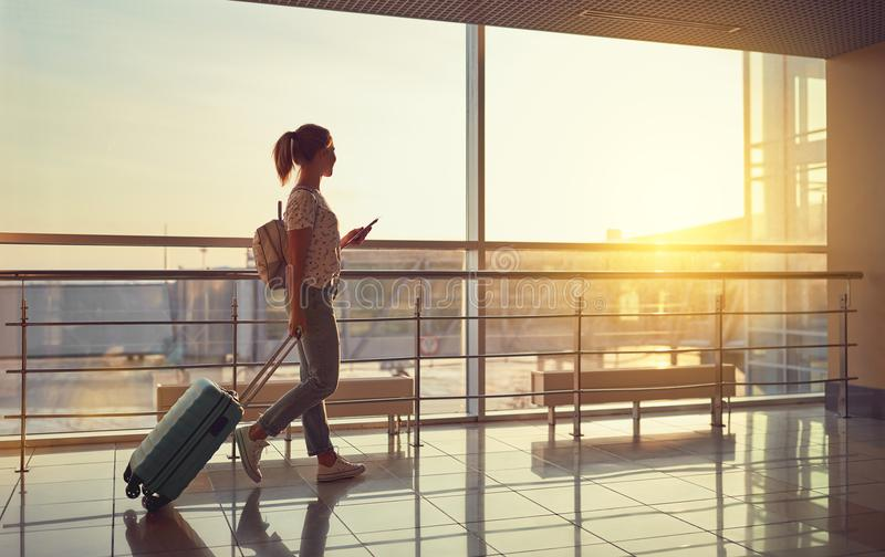 Young woman goes at airport at window with suitcase waiting for royalty free stock images