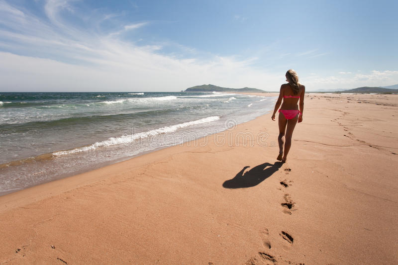 Young woman goes the distance through the empty, wild beach against a blue sky, yellow sand and sea. Wide angle. royalty free stock photography