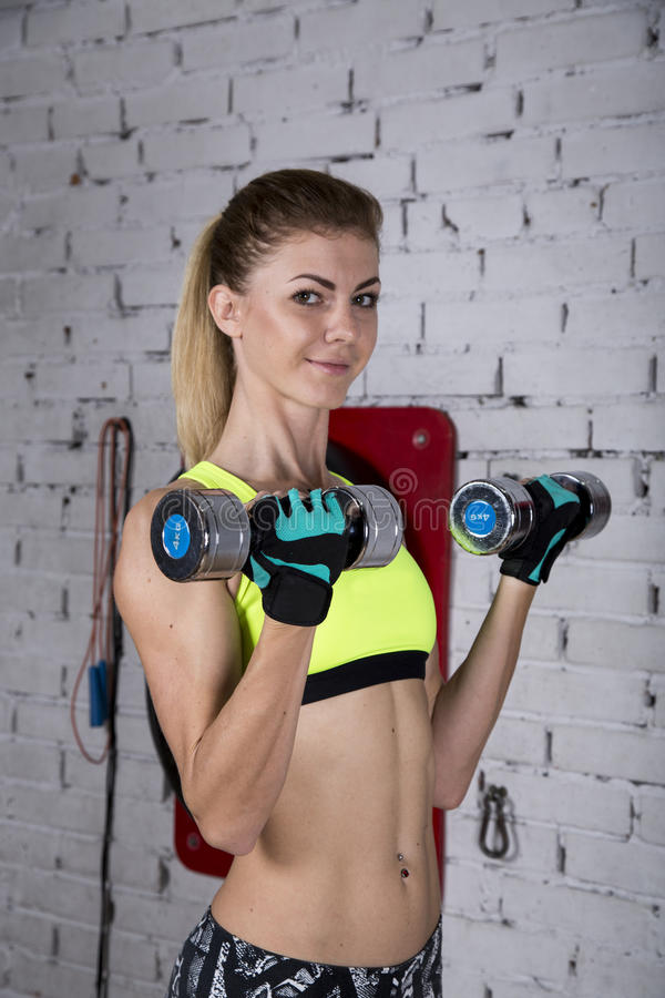 Young woman goes in for sports at gym stock photo