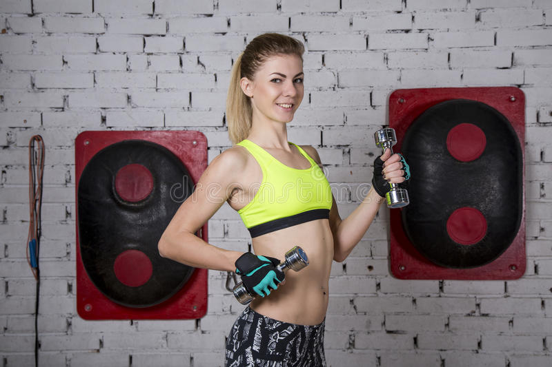 Young woman goes in for sports at gym royalty free stock photo