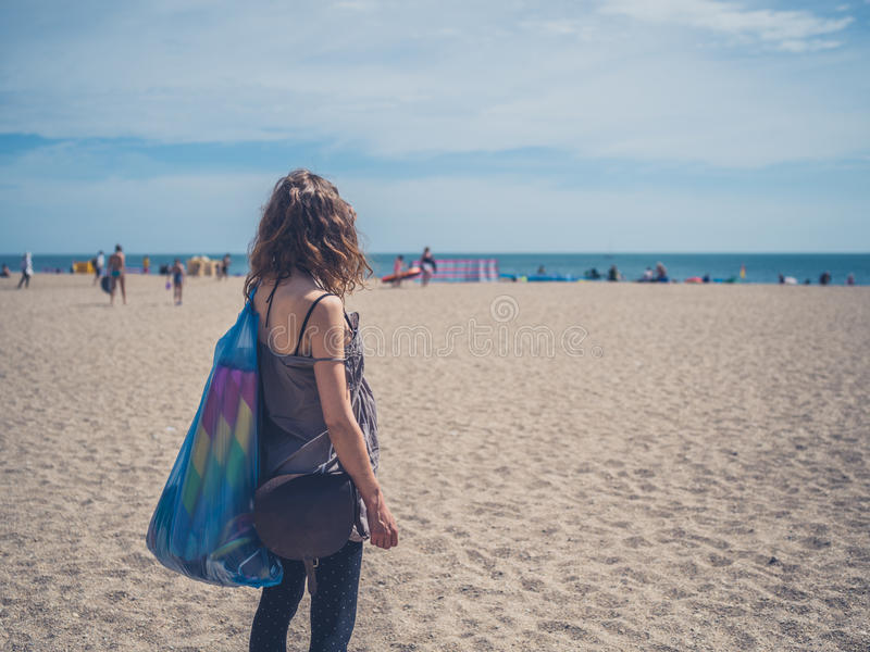 Young woman going to the beach. A young woman is going to the beach with a bag full of mats and similar items royalty free stock photography