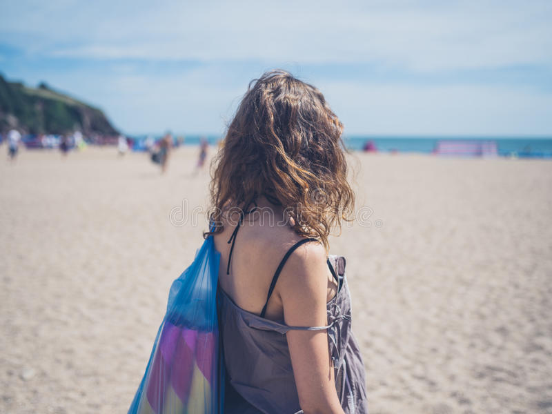 Young woman going to the beach. A young woman is going to the beach with a bag full of mats and similar items stock photography
