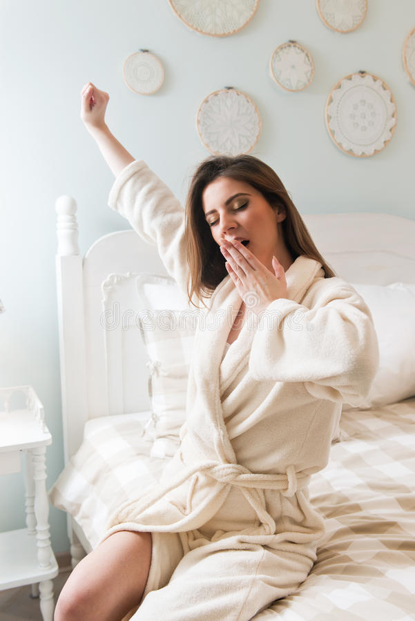 Young woman going to bed - getting out of the bed. Yawning royalty free stock photography