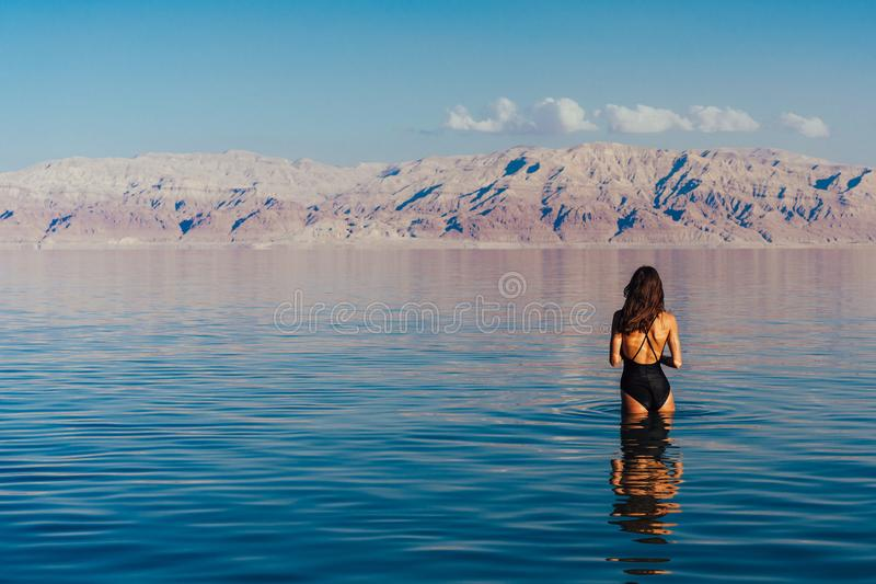 Young woman going to Dead Sea, Israel. Girl is relaxing and swimming in the water of the Dead Sea in Israel stock photos