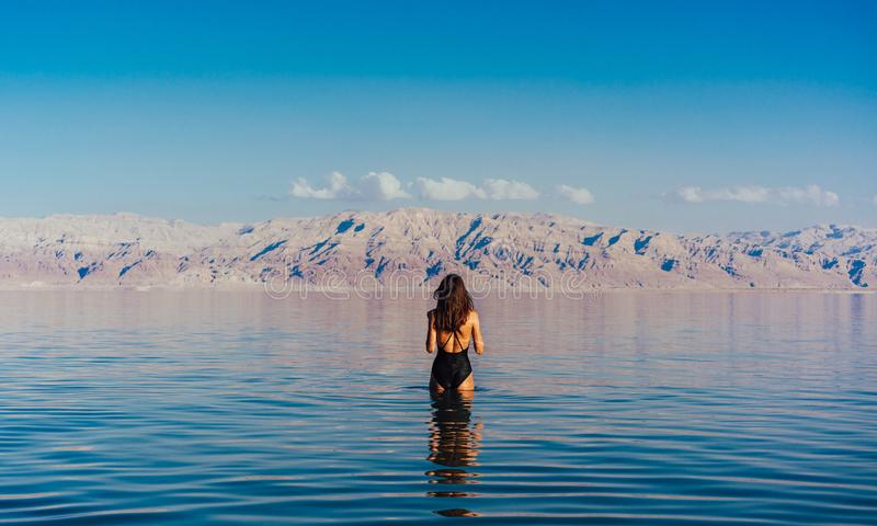 Young woman going to Dead Sea, Israel. Girl is relaxing and swimming in the water of the Dead Sea in Israel royalty free stock image