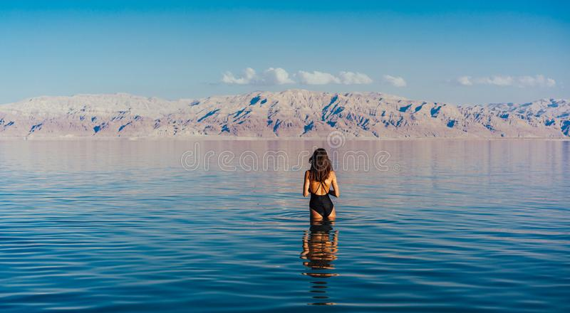 Young woman going to Dead Sea, Israel. Girl is relaxing and swimming in the water of the Dead Sea in Israel royalty free stock photography