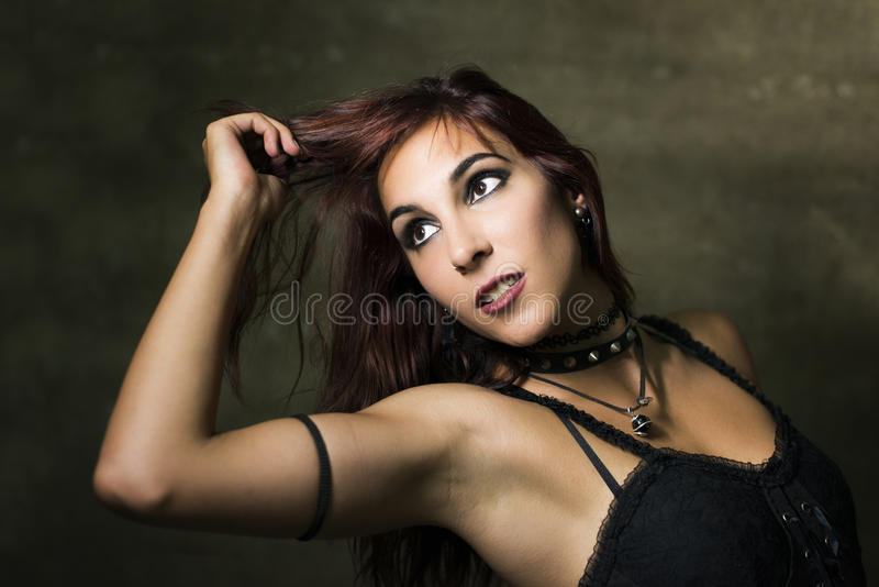 Young woman with gothic and heavy metal style posing on dirty wa. Young woman with gothic and heavy metal style and spiked collar posing on dirty wall background stock image