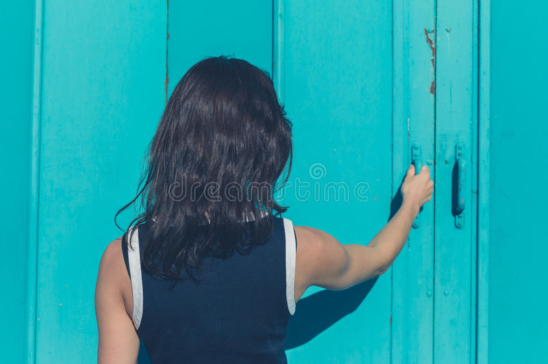 Young woman grabbing blue door royalty free stock photography