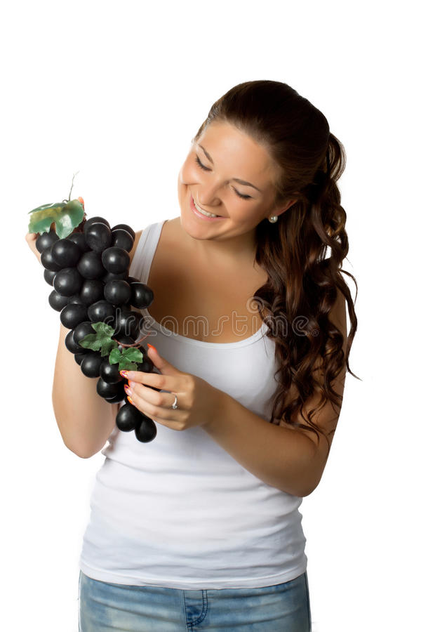 Young woman and grapes on white. Background stock photography