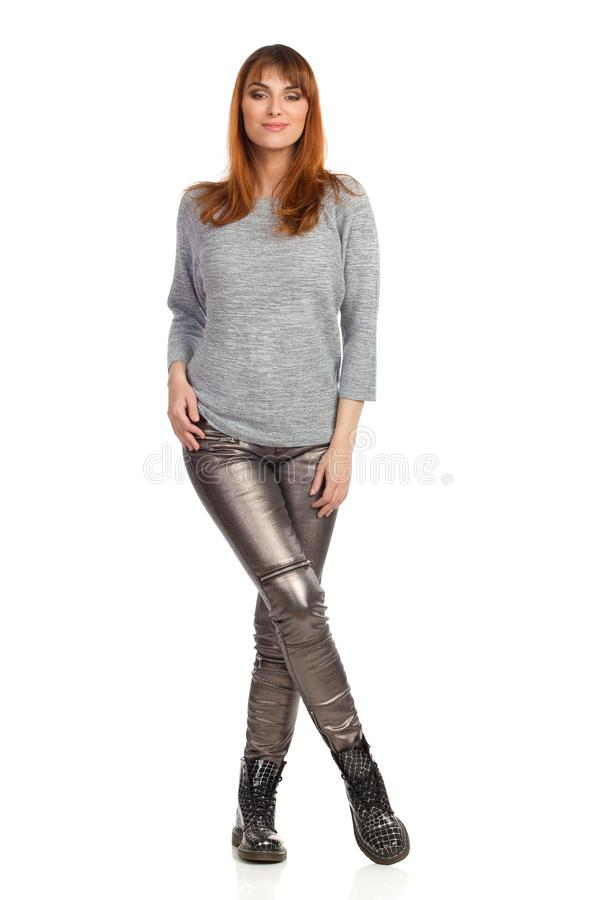 Young Woman In Gray Blouse, Shiny Pants And Black Boots Is Standing With Legs Crossed stock image