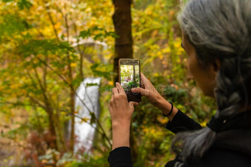 A young woman with gray hair takes photographs of the Multnomah waterfall in the Columbia River Gorge, Oregon. A young woman with gray hair takes photographs of stock photography