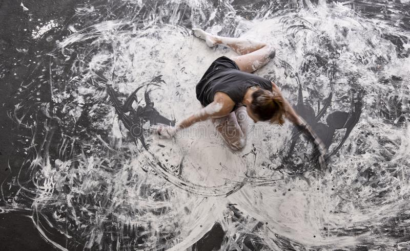 Young woman dances on the floor elegantly decorative, in gray and white color. Creative, expressive, abstract expressive body art royalty free stock photos
