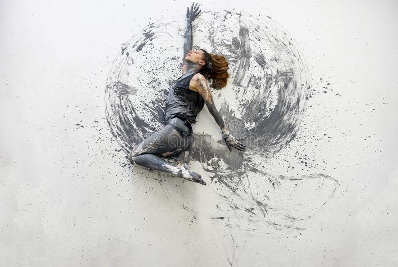 Young woman in gray shirt lies dancing dances on the floor elegantly decorative. Creative, abstract expressive body art and stock photography