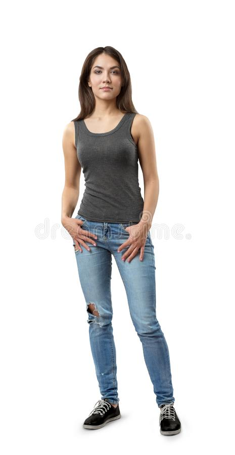 Young woman in gray sleeveless top and blue jeans standing with weight on right foot, with thumbs in pockets, isolated royalty free stock image