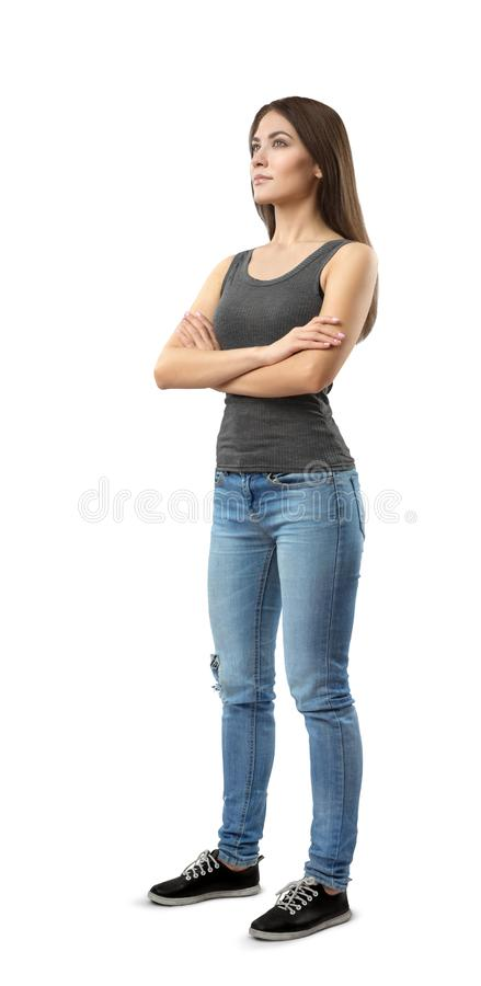 Young woman in gray top and blue jeans standing in half-turn with arms folded, looking up and away, isolated on white. Background. Dream of future. Plan things stock photos