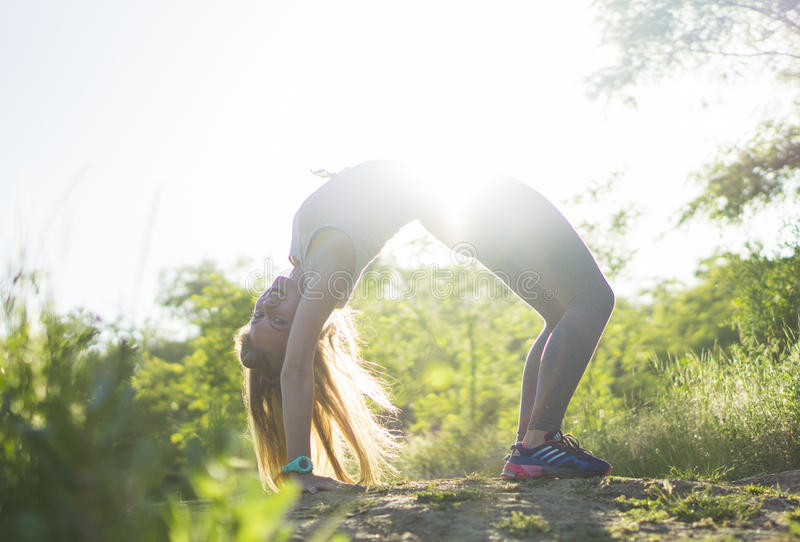 Young woman in gray top practicing yoga in beautiful nature. Stretch workout outdoor stock image