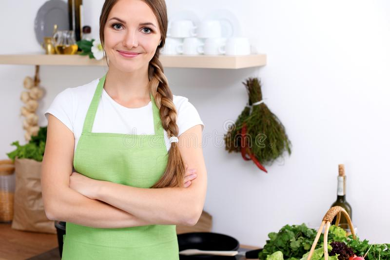 Young woman in green apron is going for cooking in a kitchen. Housewife is tasting the soup by wooden spoon. Young woman in green apron is going for cooking in royalty free stock photo