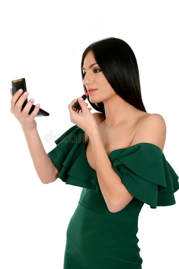 Young woman in green dress holding mirror, applying red lipstick royalty free stock image