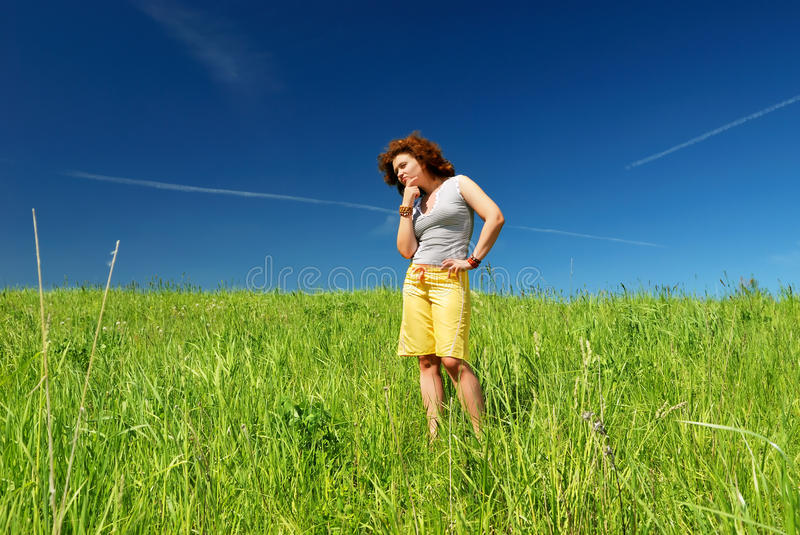 Young woman on the green field stock image