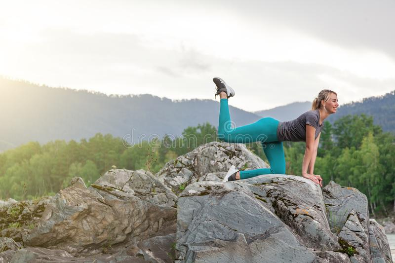 Young woman in green leggins doing the donkey kick exercise on all fours arching back straightening leg up. Concept sport, fitness stock photography