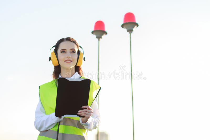 Young woman in green west and earmuffs stand on roof, hold tablet stock photo