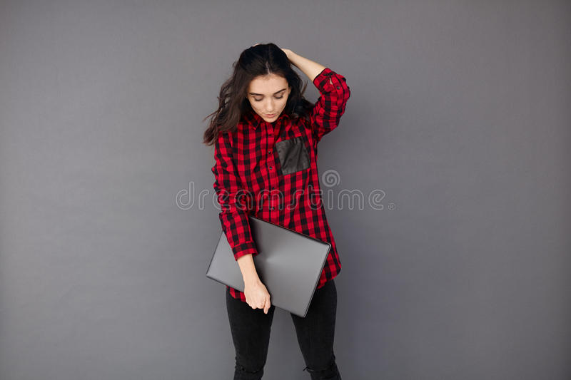 Young woman on grey background standing and holding laptop. Full length portrait of young woman on grey background standing and holding laptop computer on a grey royalty free stock images