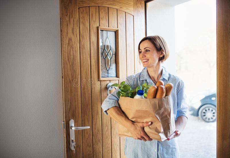 A young woman with groceries in paper shopping bag walking in through front door. royalty free stock image